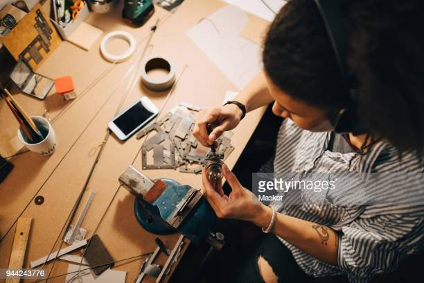 high angle view of technician working on equipment at desk in workshop - inventor stock pictures, royalty-free photos & images