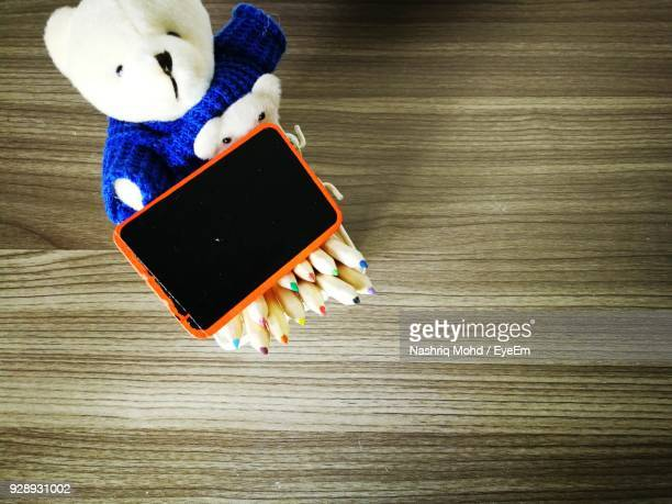 High Angle View Of Teddy Bear With Writing Slate And Pencils On Table
