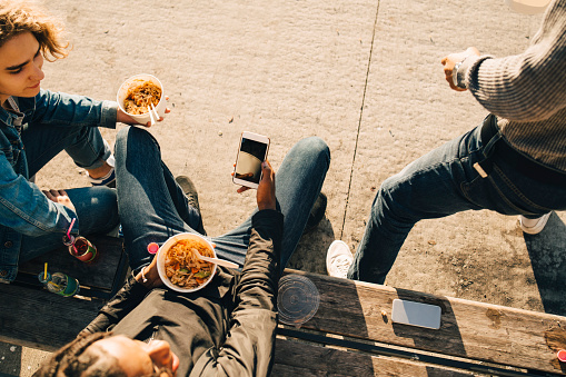 High angle view of teenage boy using smart phone while eating meal with friends on street in city - gettyimageskorea