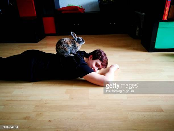 High Angle View Of Teenage Boy With Rabbit At Home