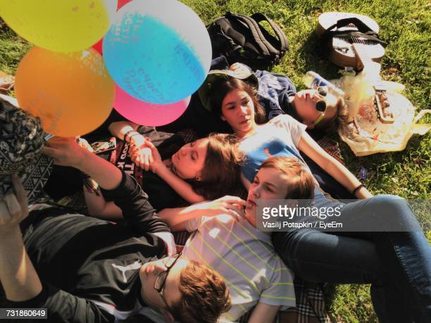 High Angle View Of Teenage Friends With Balloon Lying In Park