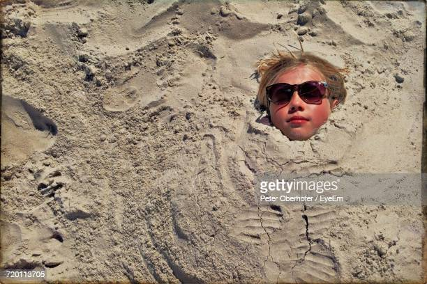 high angle view of teenage girl buried in sand at beach - 埋まる ストックフォトと画像