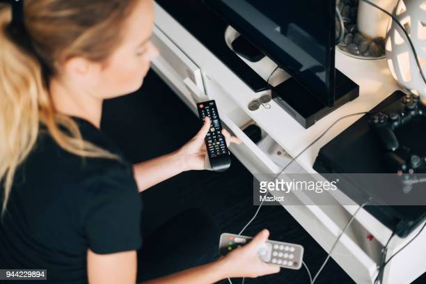 high angle view of teenage girl holding remote controls by television set in living room at home - afstandsbediening stockfoto's en -beelden