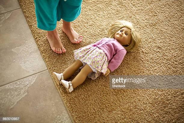 High angle view of teenage girl standing over doll