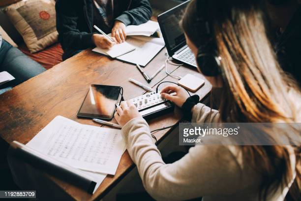 high angle view of teenage girl using audio equipment while doing homework at table in room - equaliser stock pictures, royalty-free photos & images