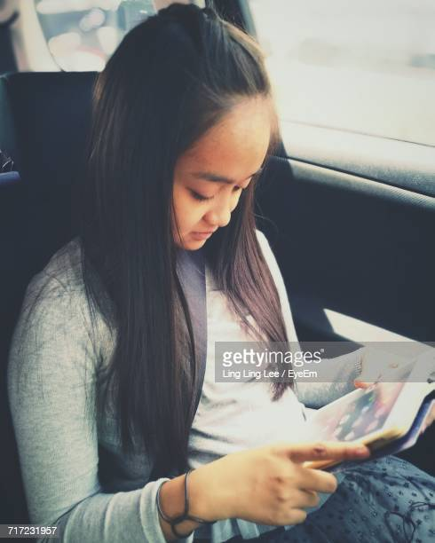 High Angle View Of Teenage Girl Using Digital Tablet While Sitting In Car