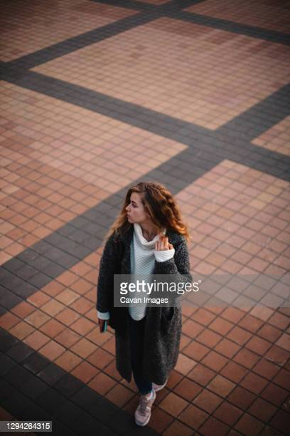 high angle view of teenage girl walking on city square in the evening - bad student stock pictures, royalty-free photos & images