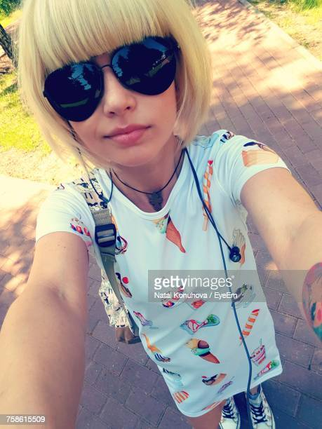 High Angle View Of Teenage Girl Wearing Sunglasses While Taking Selfie