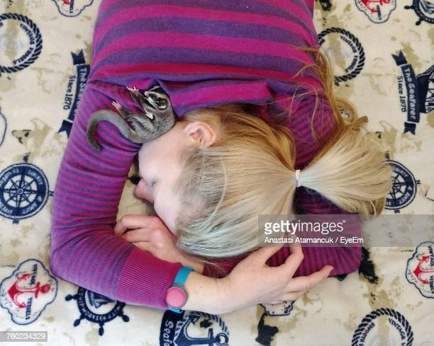 high angle view of teenage girl with sugar glider sleeping on bed at home - sugar glider stock photos and pictures
