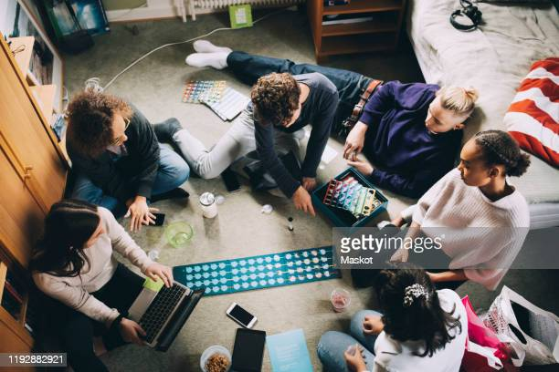 high angle view of teenage girls and boys playing board game in bedroom - game night leisure activity stock pictures, royalty-free photos & images