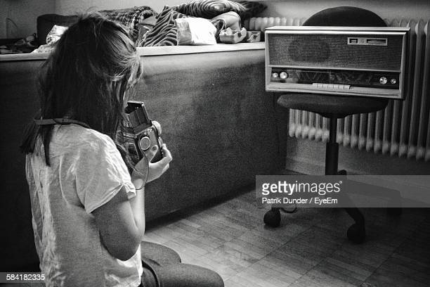 High Angle View Of Teenager Holding Camera Photographing Vintage Radio