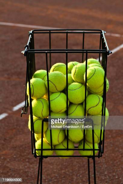 high angle view of tennis balls in basket at court - racket sport stock pictures, royalty-free photos & images