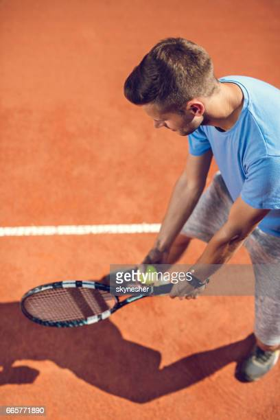 High angle view of tennis player about to serve ball.