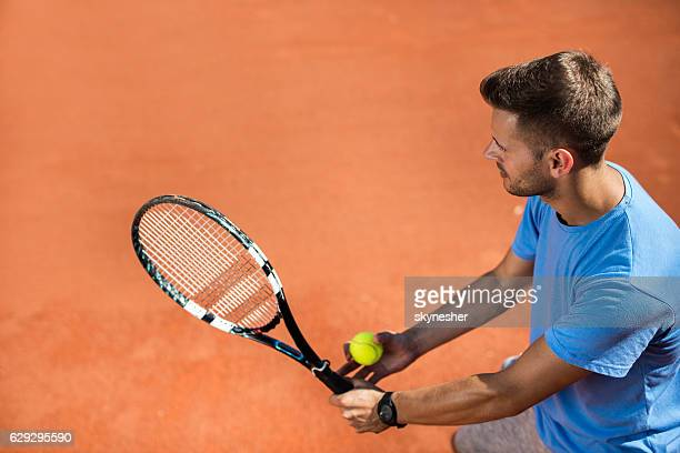 High angle view of tennis player serving the ball.