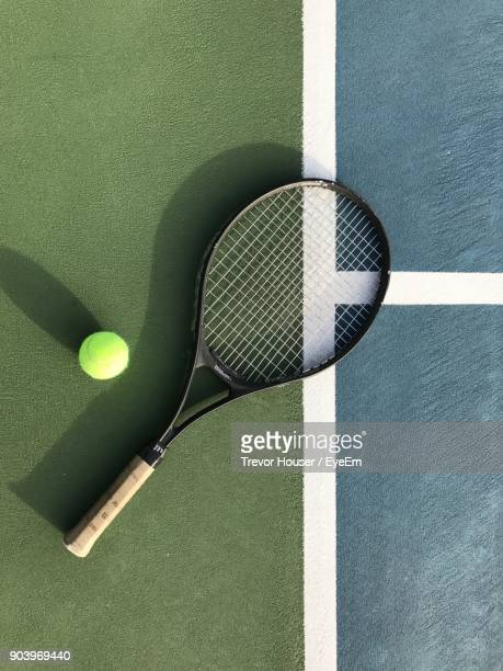 High Angle View Of Tennis Racket And Ball On Field