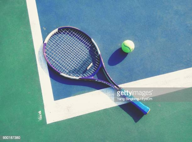 high angle view of tennis racket and ball on playing field - ラケット ストックフォトと画像