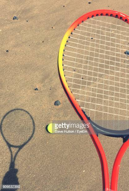 high angle view of tennis racket and ball on sand - hutton stock photos and pictures