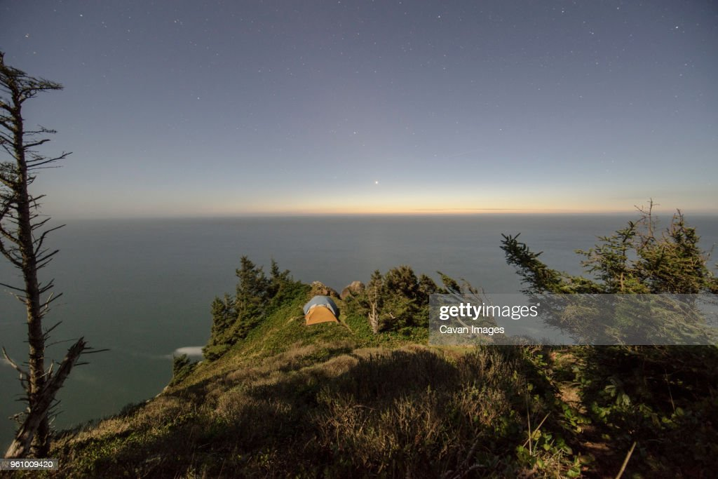 High angle view of tents on mountain by sea against sky at night : Stock Photo