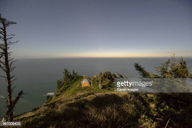 high angle view of tents on mountain by sea against sky at night - manzanita stock pictures, royalty-free photos & images