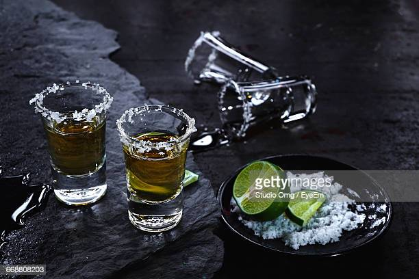High Angle View Of Tequila Shots By Lime And Salt On Table