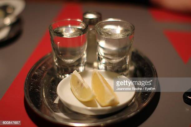 High Angle View Of Tequila Shots With Lemon Slices In Plate
