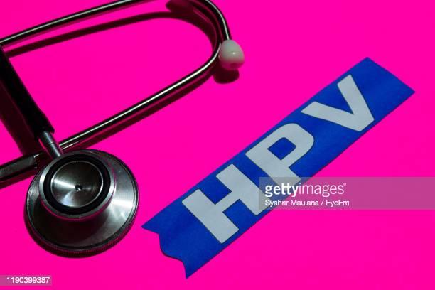 high angle view of text and stethoscope over pink background - virus del papiloma humano fotografías e imágenes de stock