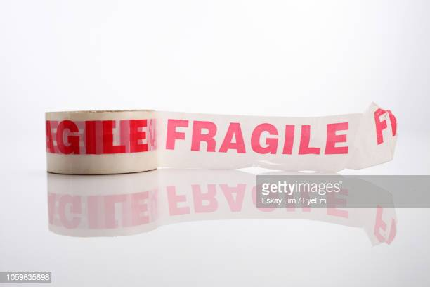 high angle view of text on adhesive tape over white background - fragilità foto e immagini stock