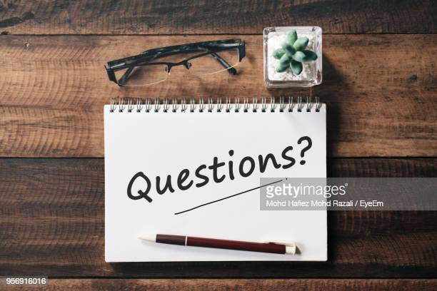 high angle view of text on book with eyeglasses by plant and pen - questions stock pictures, royalty-free photos & images