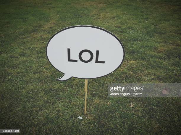 high angle view of text on speech bubble shape sign board at grassy field - quotation text stock photos and pictures