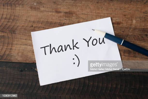 High Angle View Of Thank You Text On Paper With Pen On Wooden Table