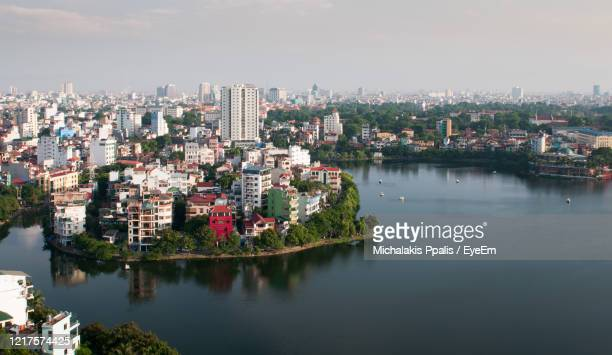 high angle view of the city of hanoi in vietnam with buildings by river against sky - ハノイ ストックフォトと画像