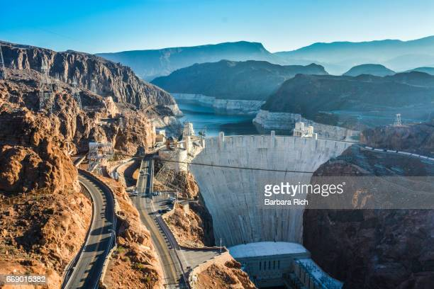 high angle view of the hoover dam taken from the pedestrian walkway bridge over the colorado river on hwy 93 in the early  morning light. - hoover dam stock photos and pictures