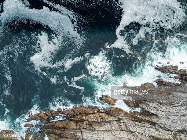 high angle view of the waves crashing against the sea - rock overhang stock photos and pictures