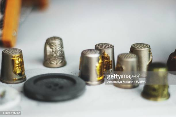 high angle view of thimbles and sewing button on table - thimble stock photos and pictures