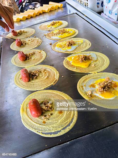 high angle view of thosais cooking with sausages and eggs on pan - dosa stock photos and pictures