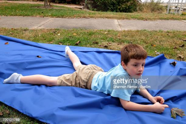 high angle view of thoughtful boy lying on blue sheet in yard - lying on front stock pictures, royalty-free photos & images