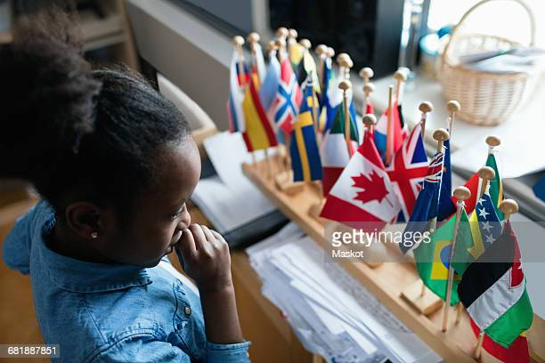High angle view of thoughtful girl looking at various flags in classroom