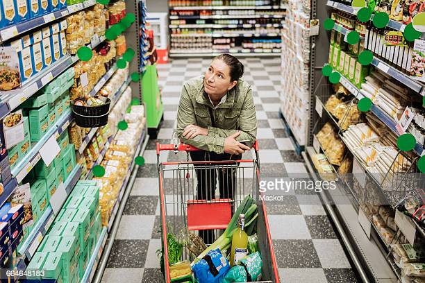 High angle view of thoughtful woman leaning on shopping cart at supermarket