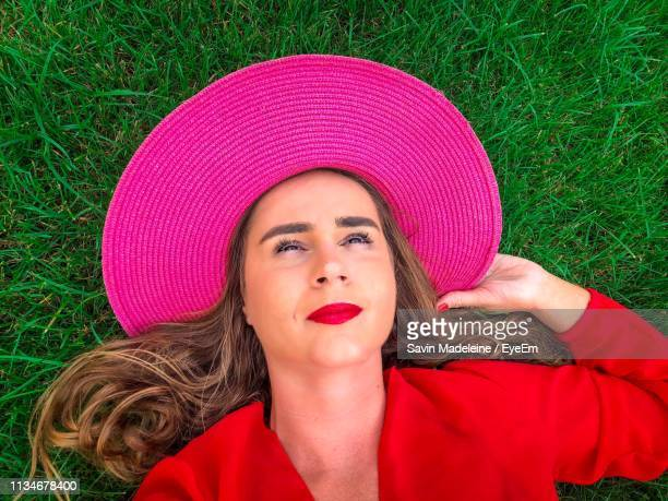 high angle view of thoughtful woman wearing pink hat while lying on grassy field - lady madeleine stock-fotos und bilder