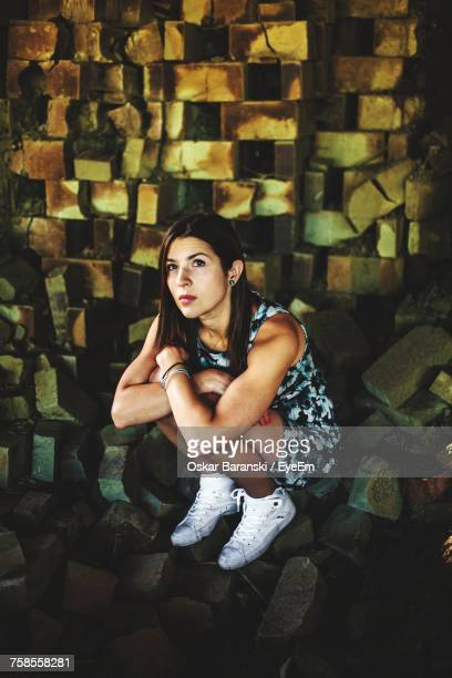 high angle view of thoughtful young woman crouching on broken paving stones - woman in broken shoe heel stock pictures, royalty-free photos & images
