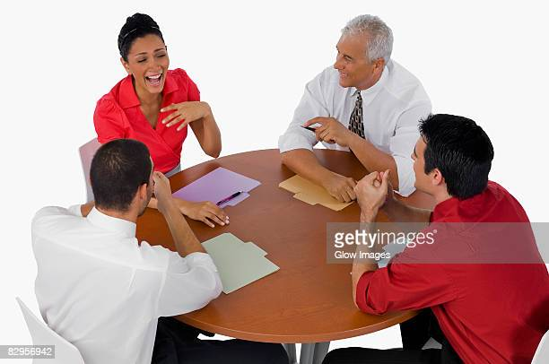High angle view of three businessmen and a businesswoman laughing in a meeting