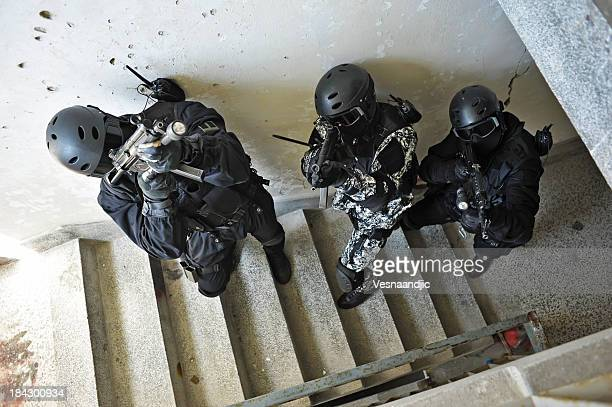 High angle view of three SWAT team members ascending stairs