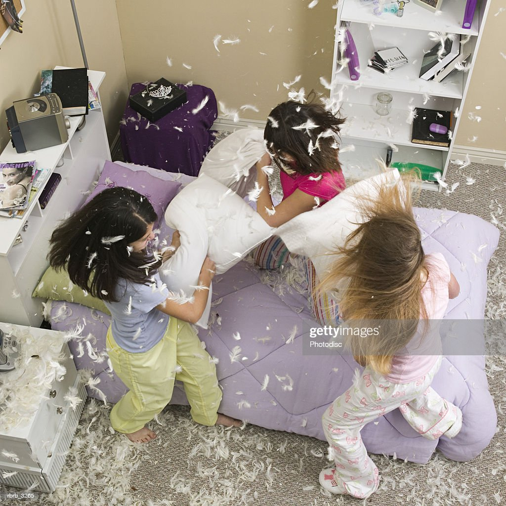 High angle view of three teenage girls having a pillow fight : Foto de stock