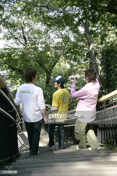High angle view of three young men walking down steps