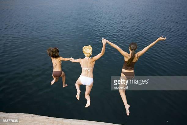 high angle view of three young women jumping into a lake - femme blonde en maillot de bain vue de dos photos et images de collection