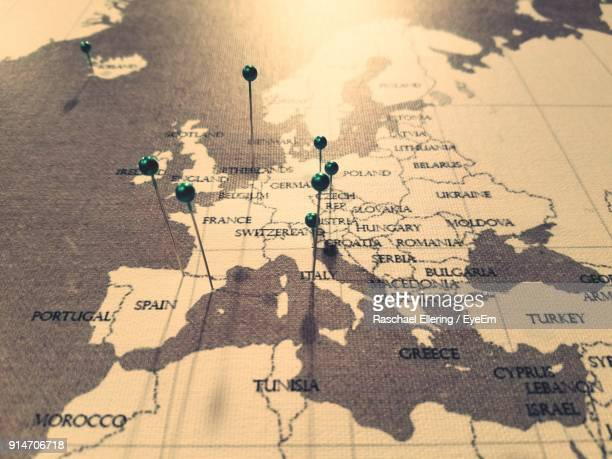 high angle view of thumbtacks on map - europe stock pictures, royalty-free photos & images