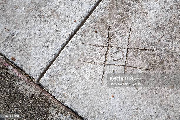 High Angle View Of Tic-Tac-Toe Carved On Footpath
