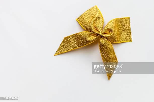 high angle view of tied bow on white background - knoop naaigerei stockfoto's en -beelden