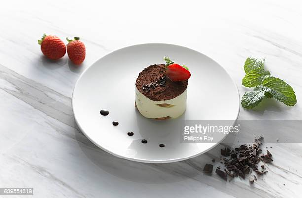 High angle view of tiramisu on plate with fresh strawberries