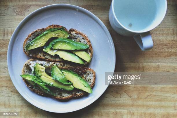 high angle view of toasted breads with avocados in plate on table - avocado toast stockfoto's en -beelden